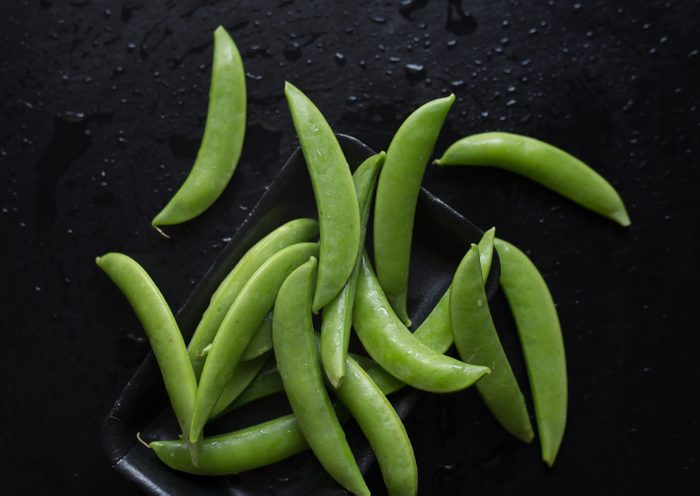 High Angle View Of Sugar Snap Peas In Tray On Wet Table