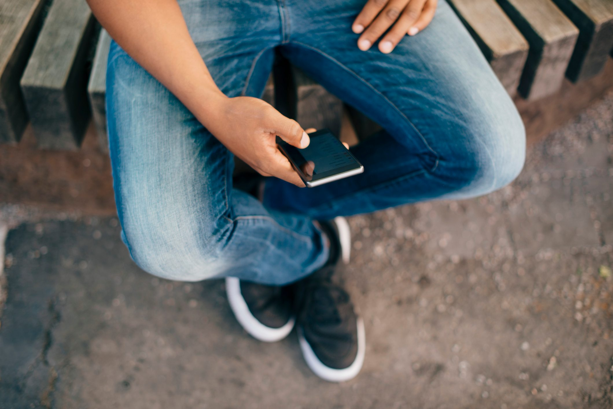 Low section of young man using smart phone while sitting on bench in city