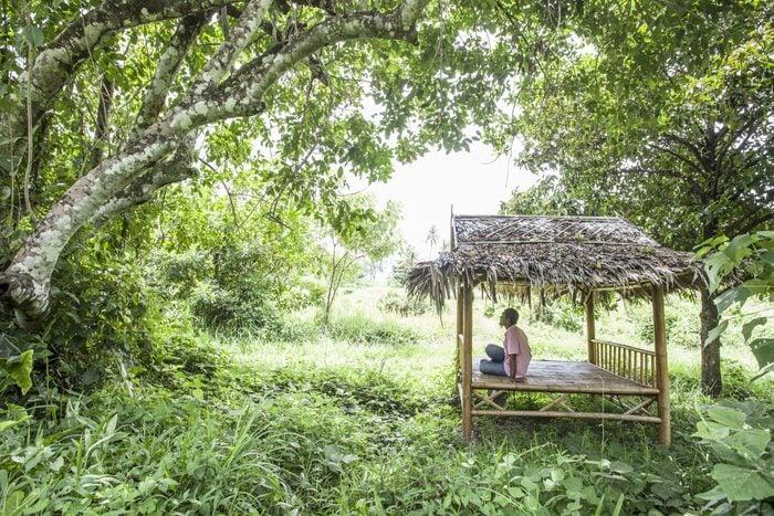 Man sitting in bamboo hut in the jungle