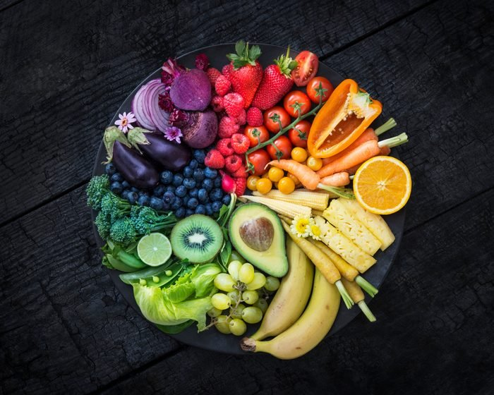 Multicoloured fruit and vegetables in a black bowl on a burnt surface.