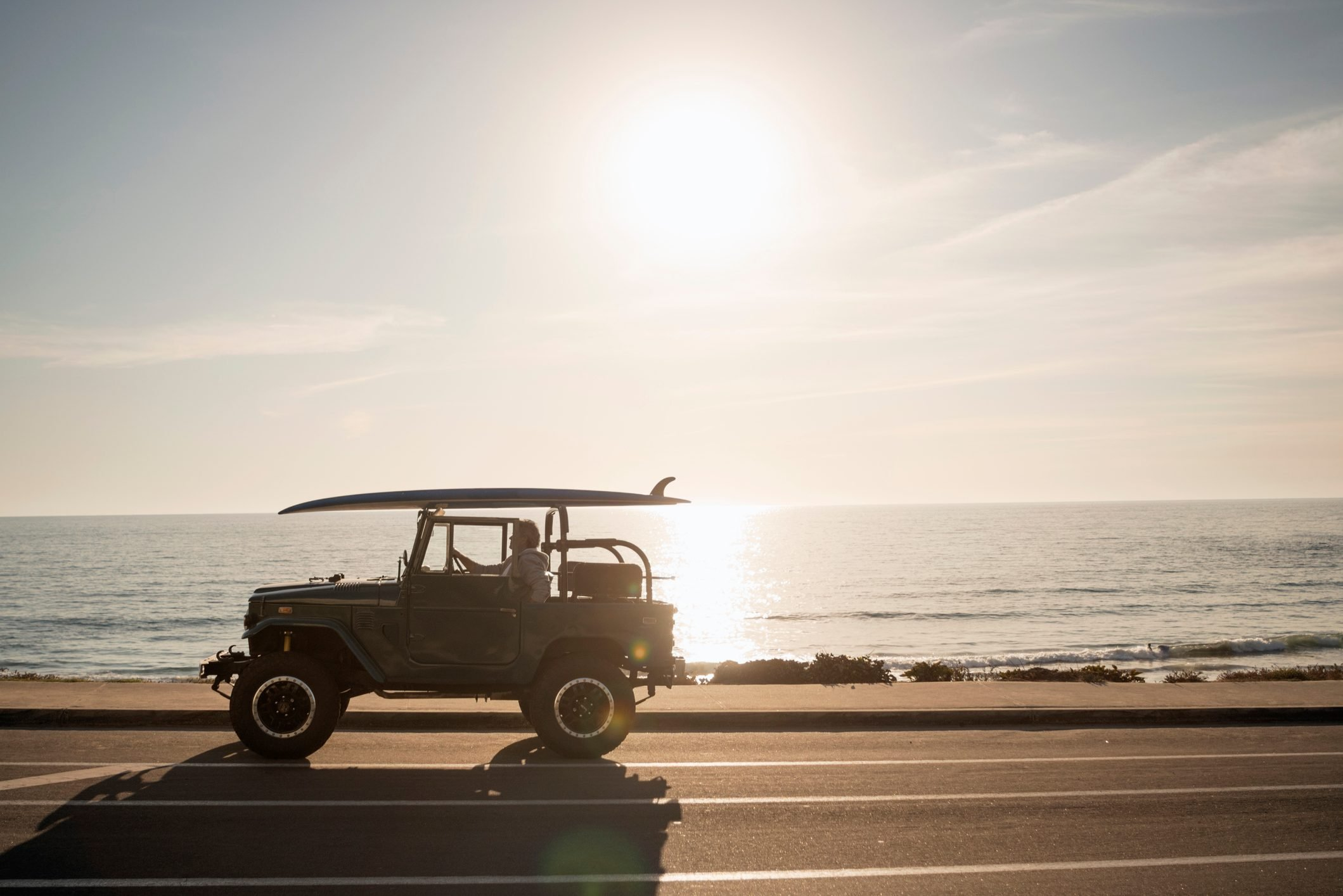 Mature man sitting in his Land Cruiser by the beach