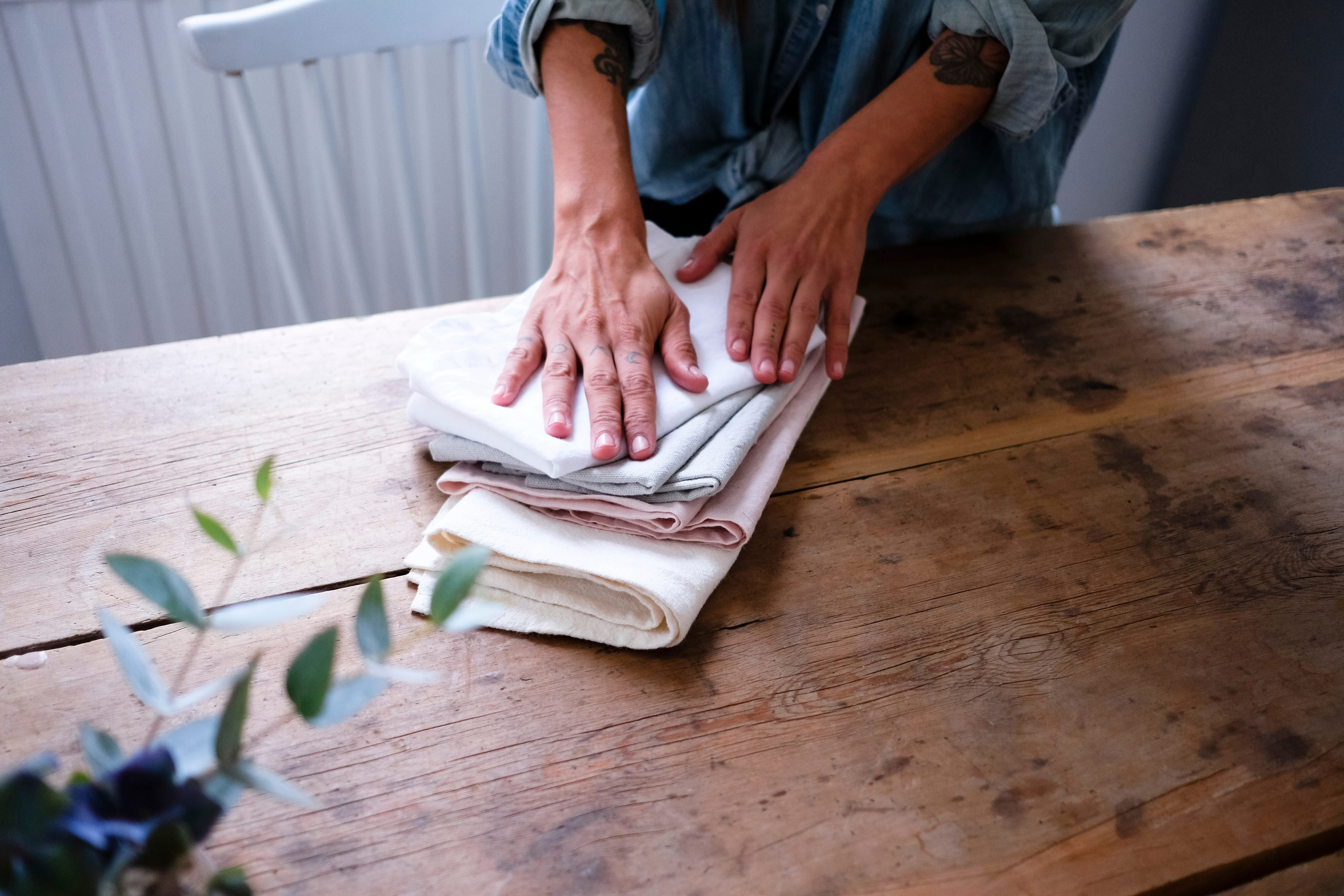 Midsection of woman folding napkins while standing at wooden table in kitchen