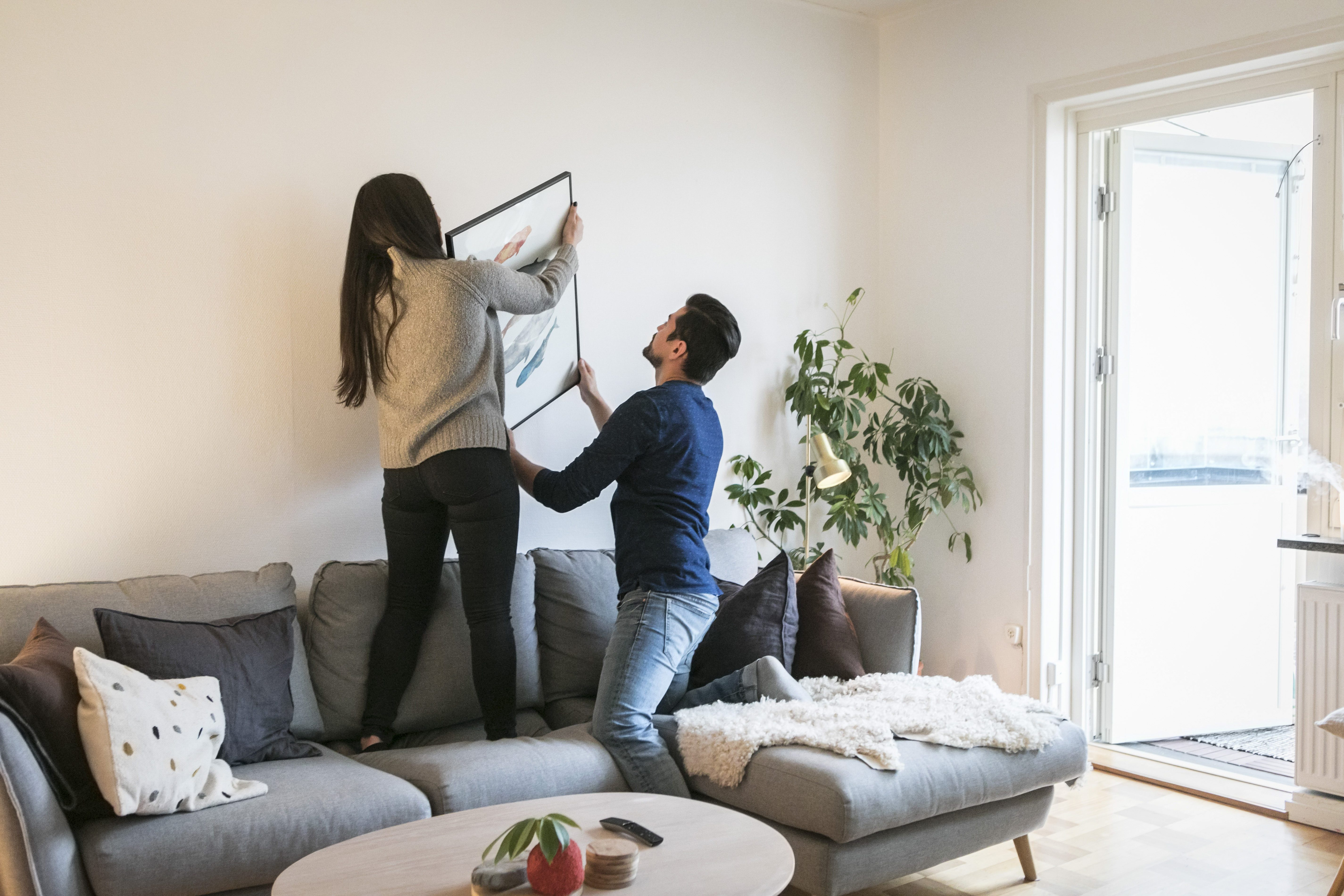 Couple adjusting painting on wall while leaning on sofa at home