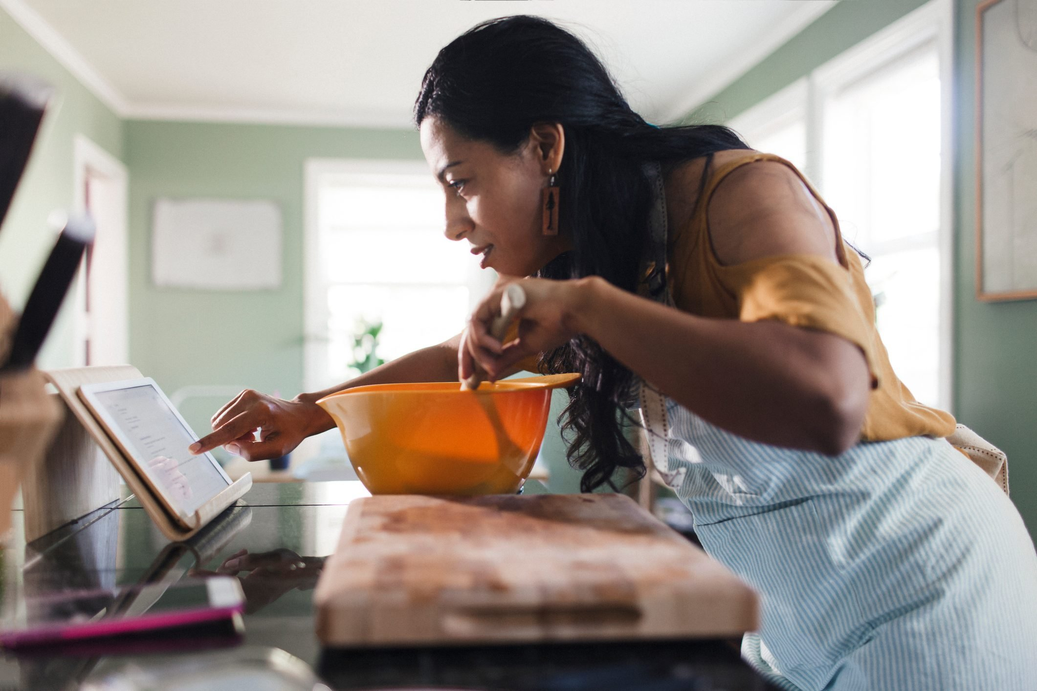 Side view of woman using tablet computer for recipe while preparing food in kitchen
