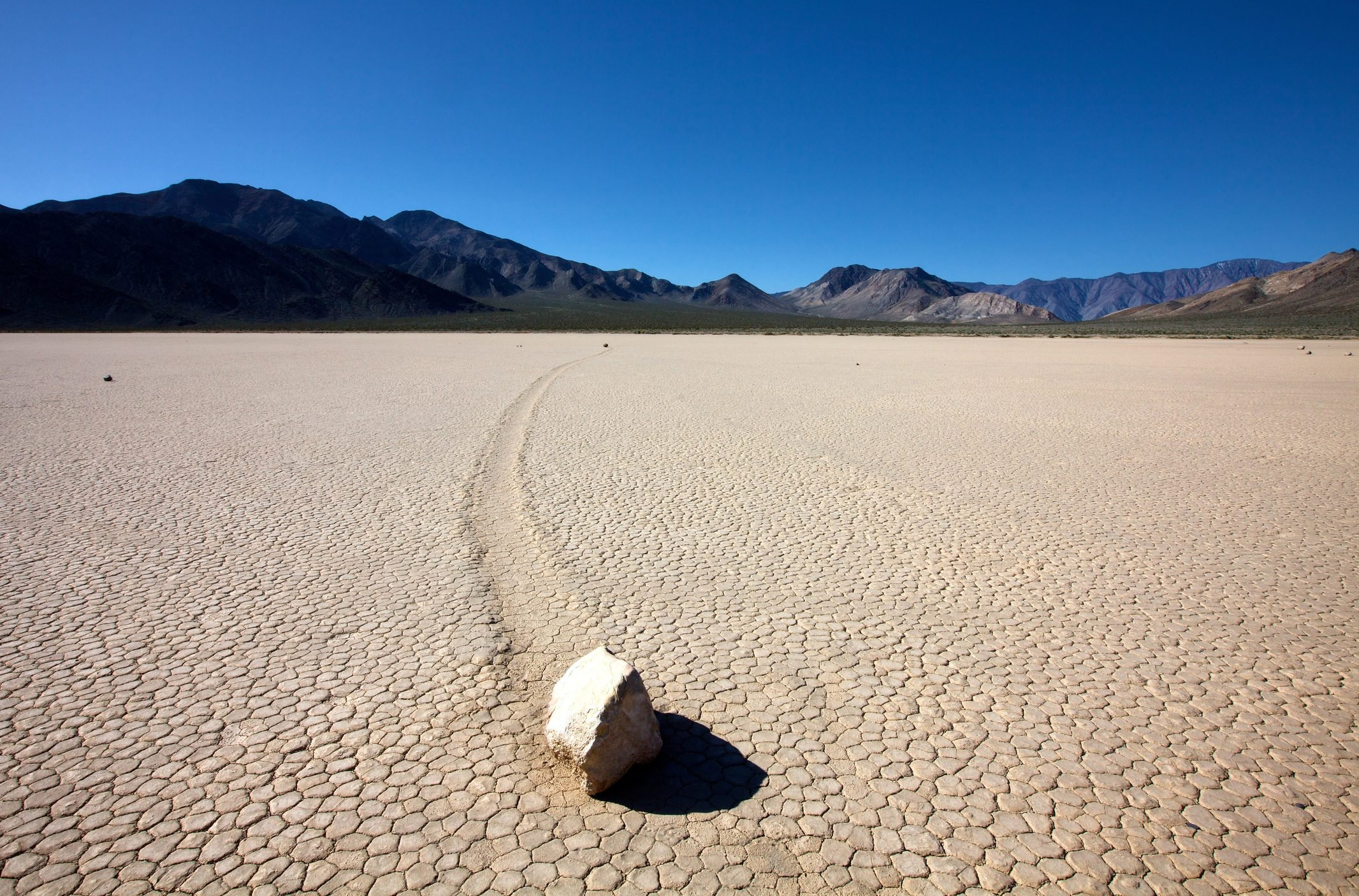 Rock and track in Racetrack Playa, Death Valley National Park, California, USA