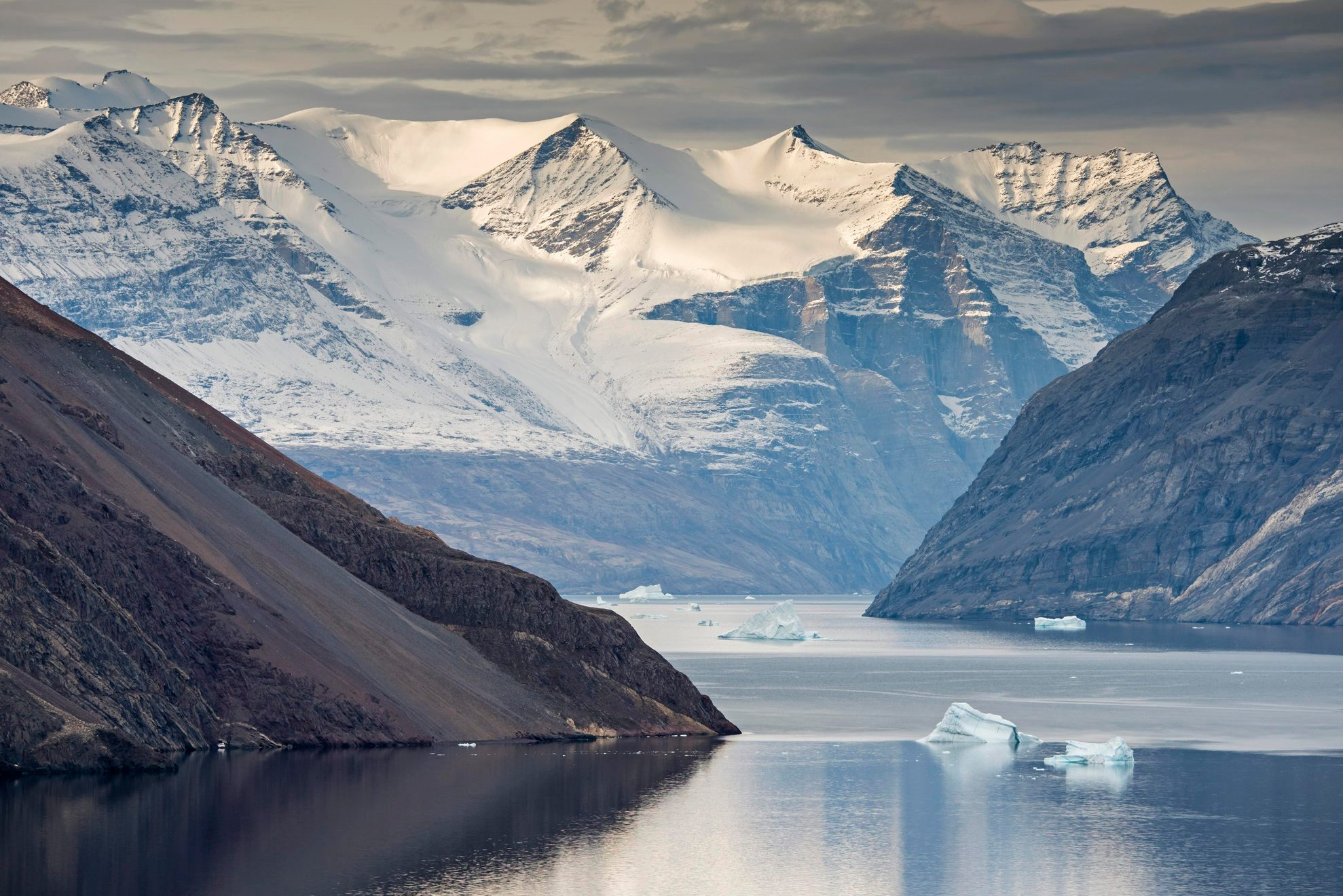 Mountain slopes and snowy mountains, icebergs in the Blomsterbugten, Kejser Franz Joseph Fjord, Northeast Greenland National Park, Greenland