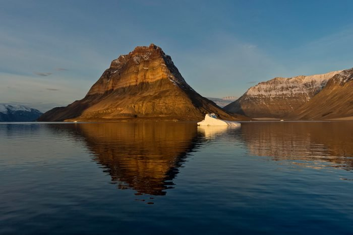 Iceberg in front of Devil's Castle mountain, Kejser Franz Joseph Fjord, Northeast Greenland National Park, Greenland