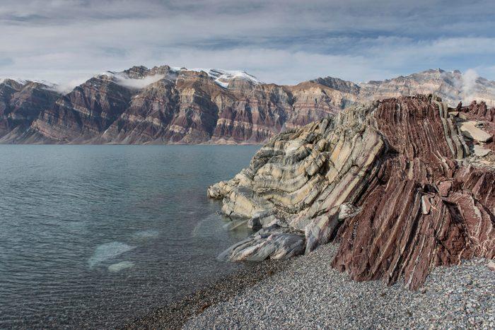 Stony beach and unfolded coloured rock strata, former marine sediments, Berzelius Bjerg, Segelsaellskapet or Segelselskapets Fjord, Northeast Greenland National Park, Greenland