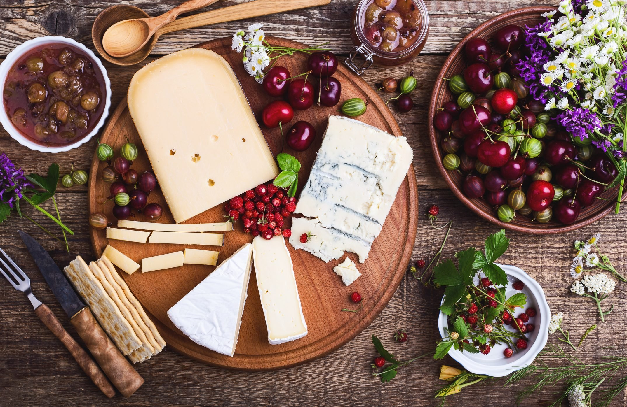 Cheese platter with fresh colorful summer berries