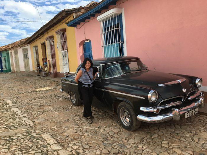 woman standing near old black car