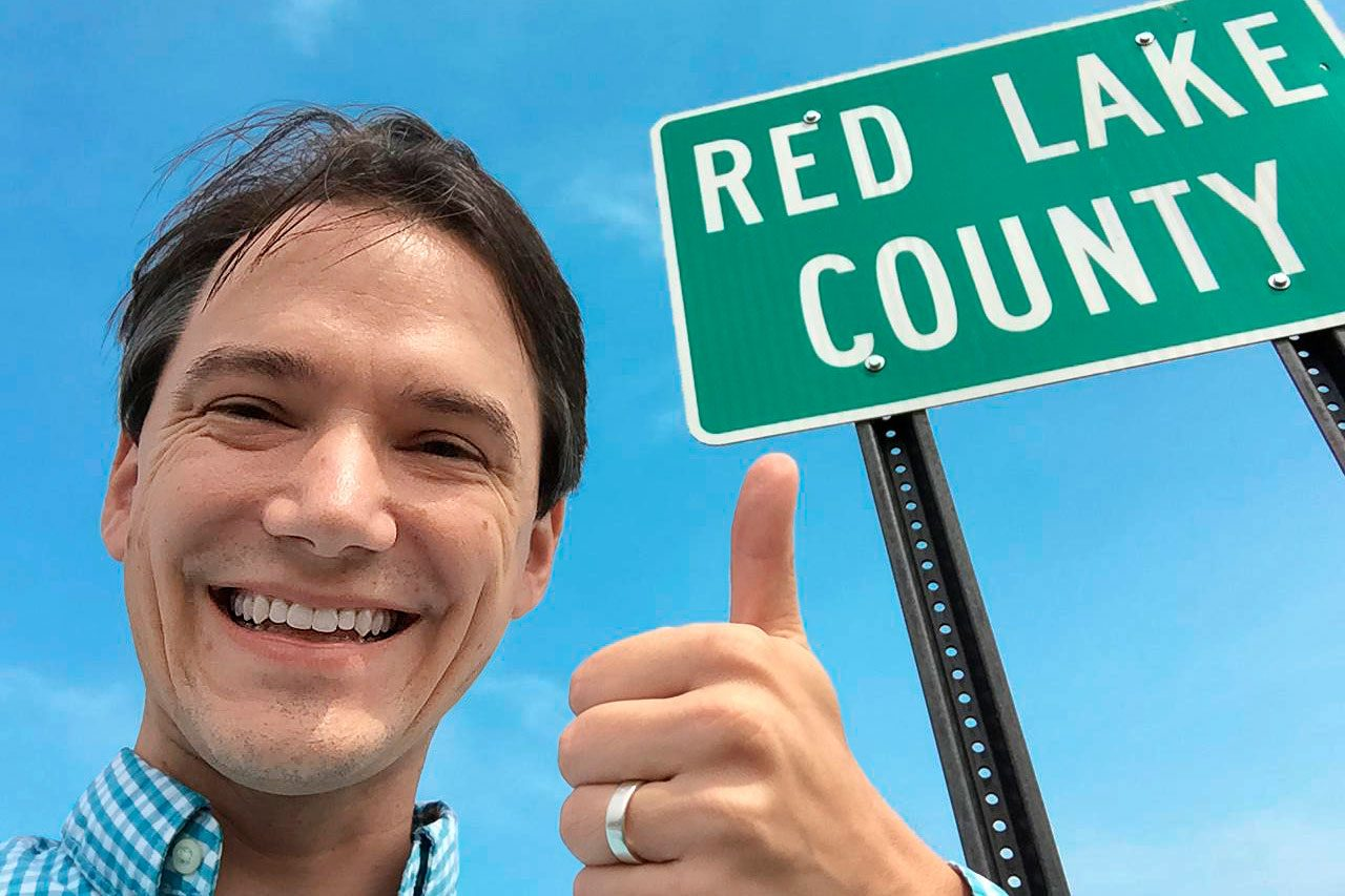 "Christopher Ingraham selfie with a sign that reads ""Red Lake County"""