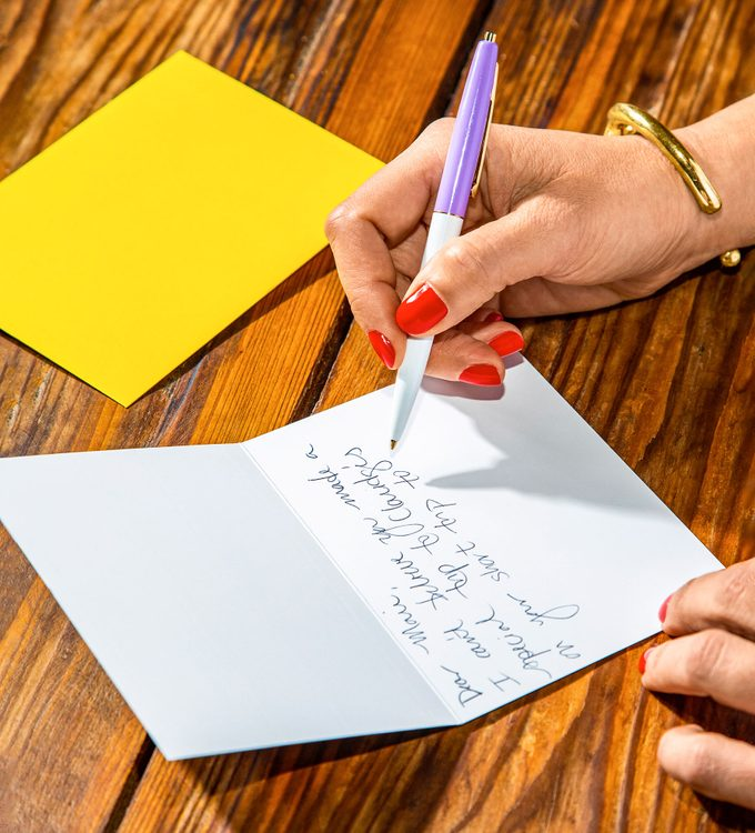 close up of Gina's hand writing a thank you note