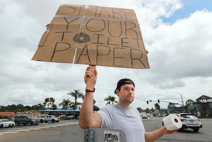 """Jonny Blue holding his sign that reads, """"share your toilet paper"""""""