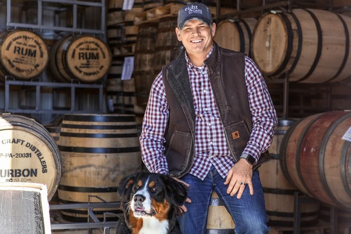 Chad Butters standing in front of barrels at Eight Oaks Farm Distillery