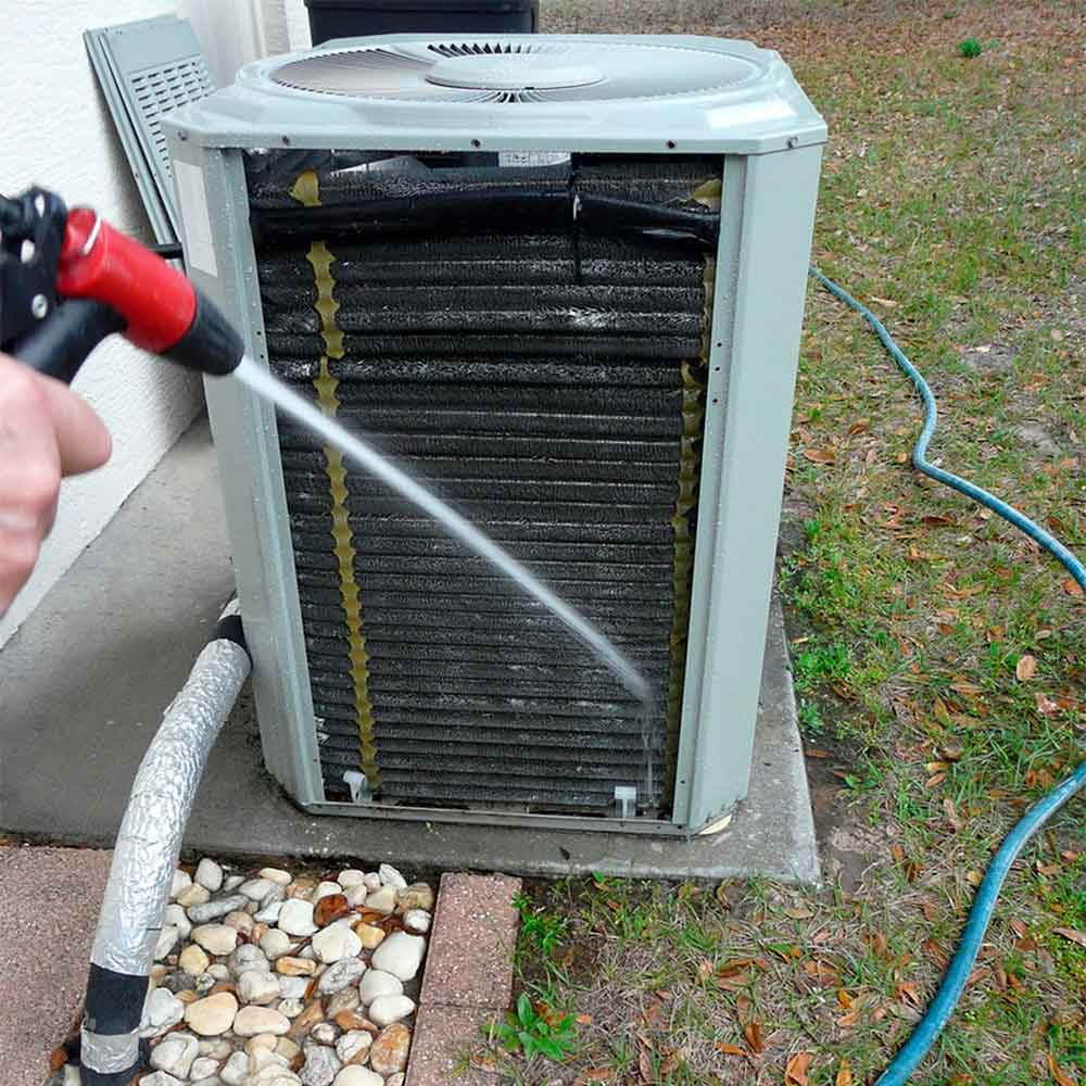 man spraying air conditioner with a hose