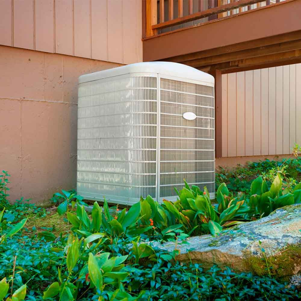 A residential central air conditioning and heating unit sitting outside a home.