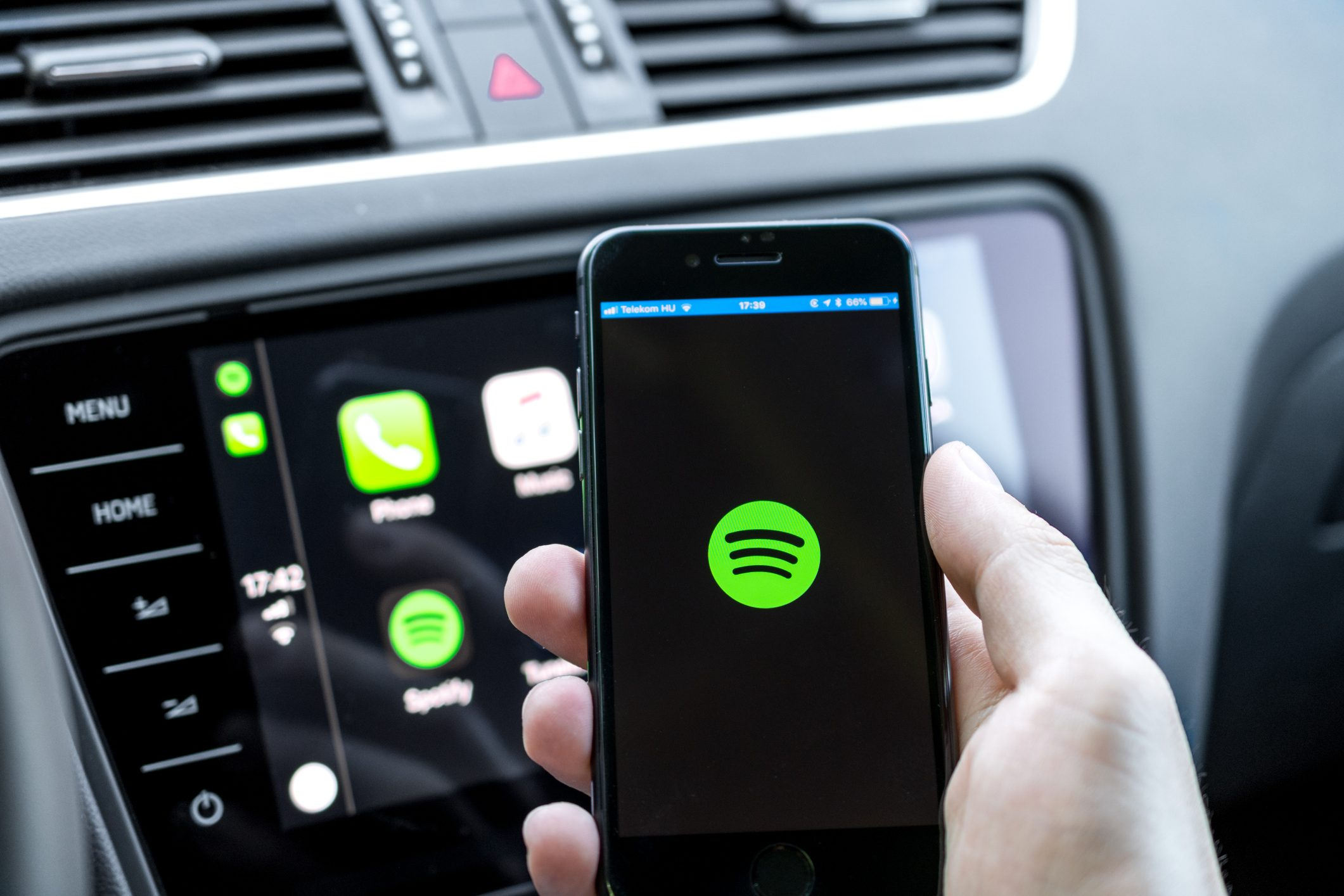 Male hands holding a smartphone that is connecting to the car's computer running the popular music streaming service
