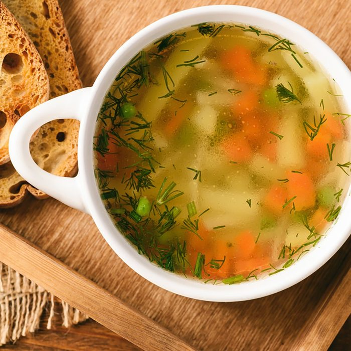 Chicken soup in white bowl on wooden tray.