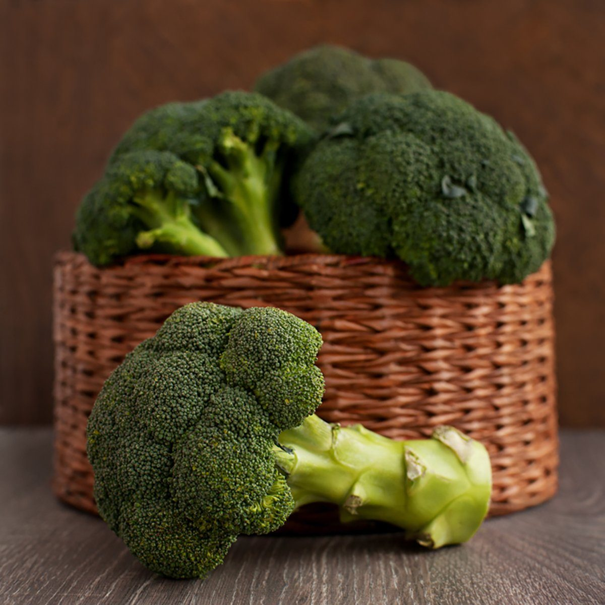 Broccoli cabbage in a wicker basket. A lot of broccoli in a wicker box on a brown background.