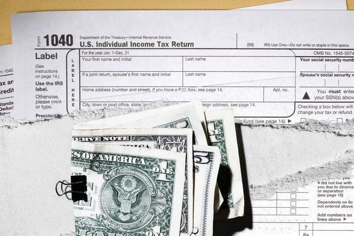 ripped tax form under wad of bills