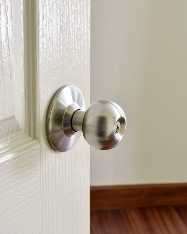 Close up of stainless metal door knob on a white painted door opening into a room.