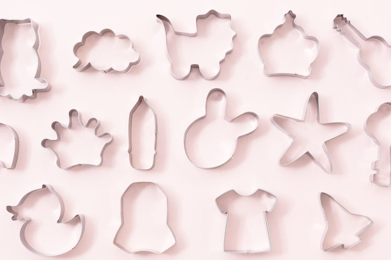 Cookies figures different shapes, top view, flat lay. Festive cookie cutters over white pink background. Tin biscuit cutters, tool to cut cookie dough. Figures for Easter, Christmas, child birthday