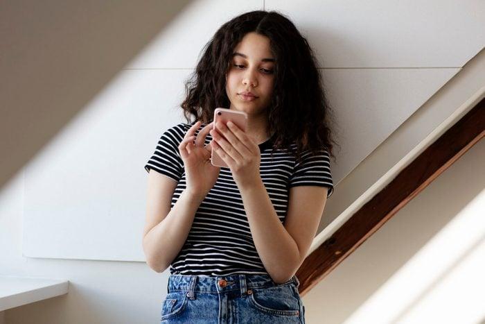 Teenage girl texting in room