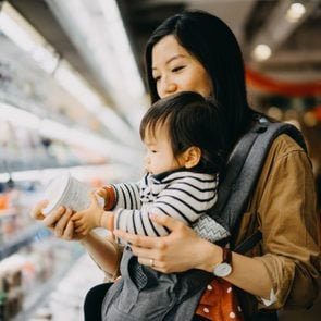 Mother carrying cute baby girl grocery shopping in supermarket and reading nutrition label on the package of fresh yoghurt