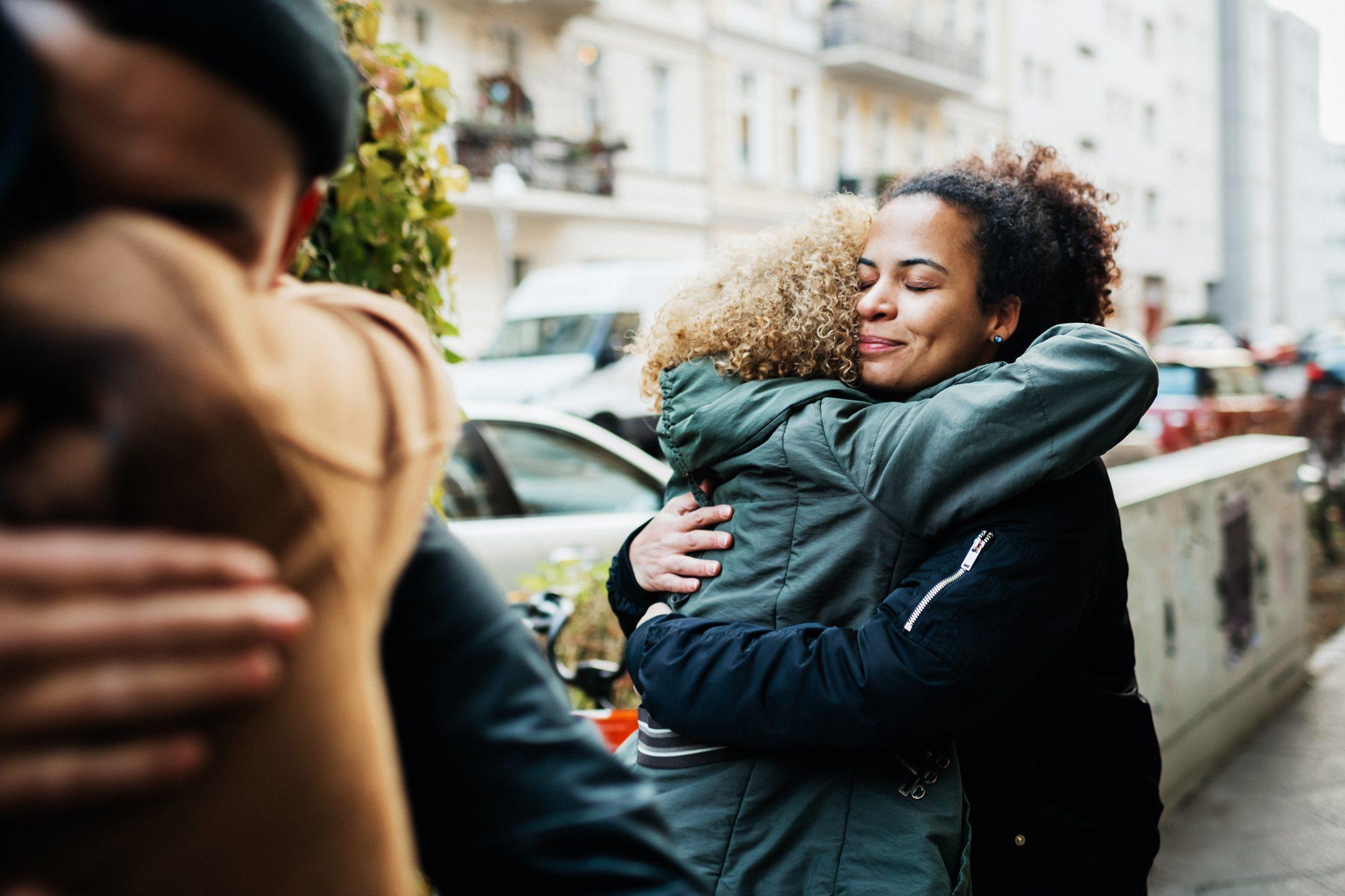 Friends Embracing In Street