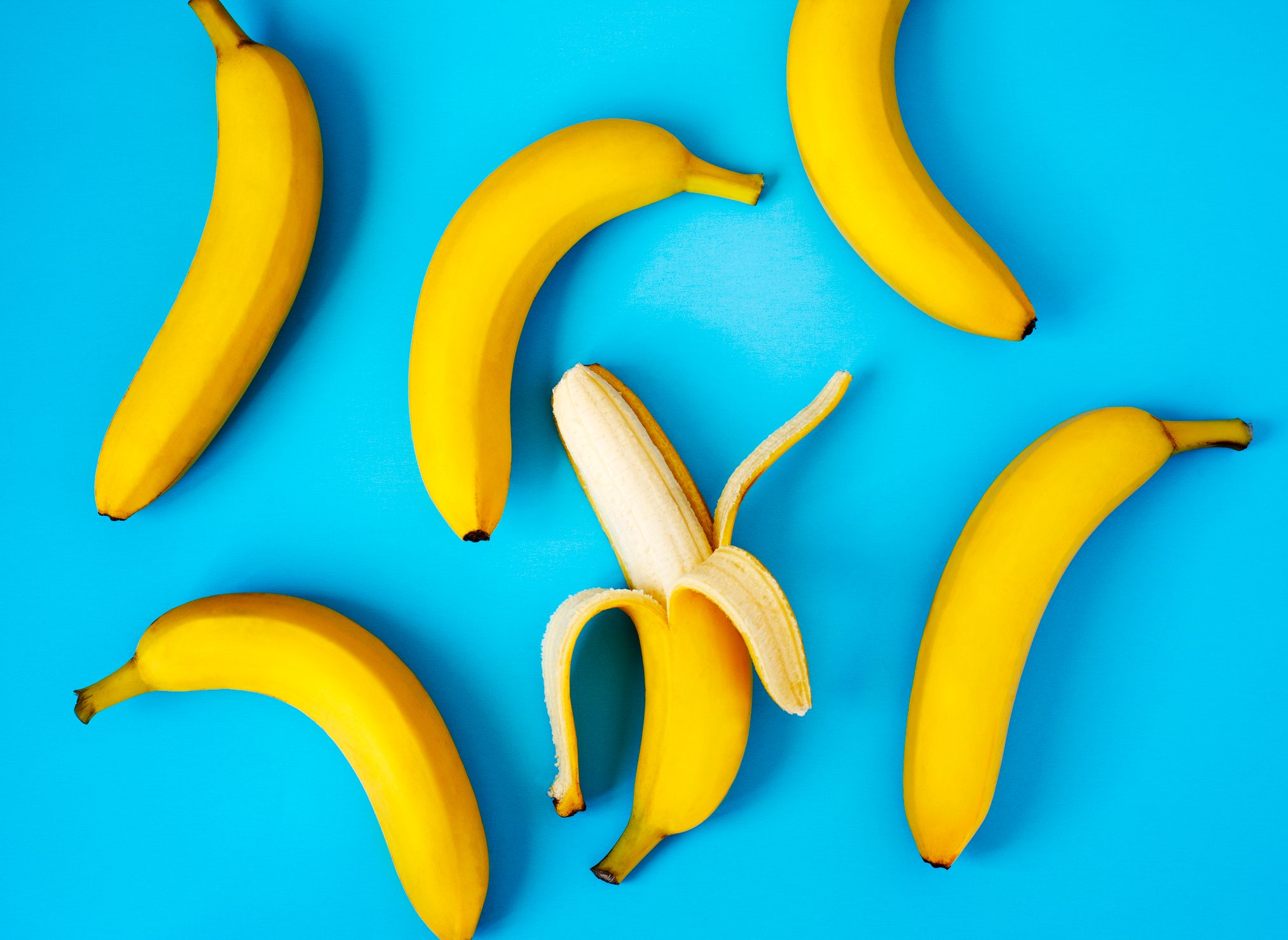 Ripe bananas on blue background