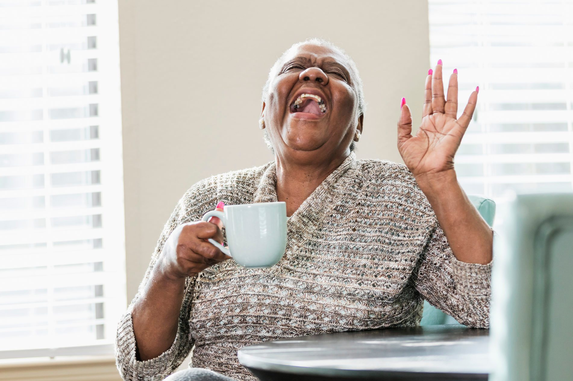 Happy senior African-American woman at home, coffee