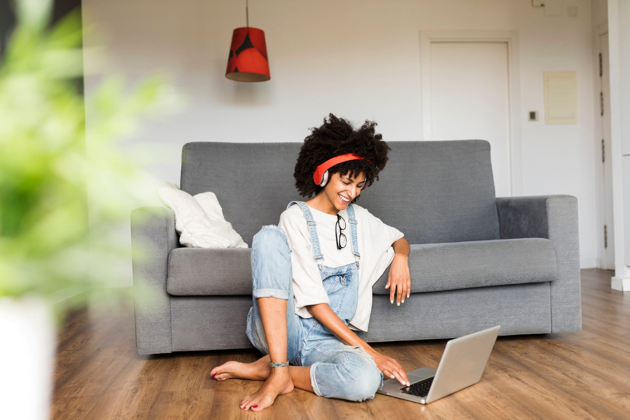 Smiling woman sitting at home with headphones and laptop
