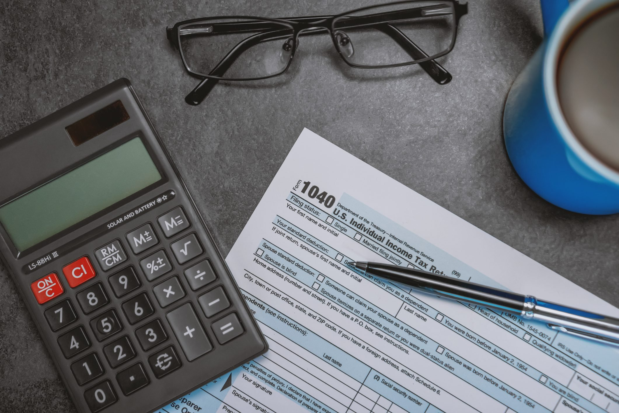 Printed Tax Form on Work Desk with Calculator and Pen