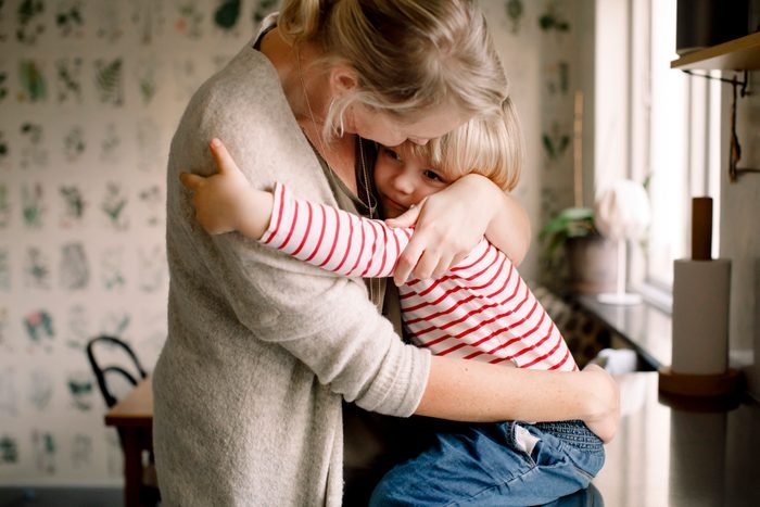 Loving daughter embracing mother while sitting on kitchen counter at home