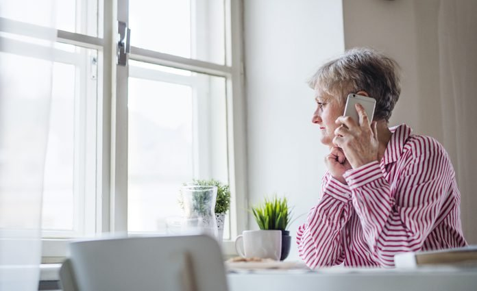 An active senior woman working in home office, lusing smartphone.