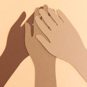 paper cutouts of diverse hands coming together. bipoc.