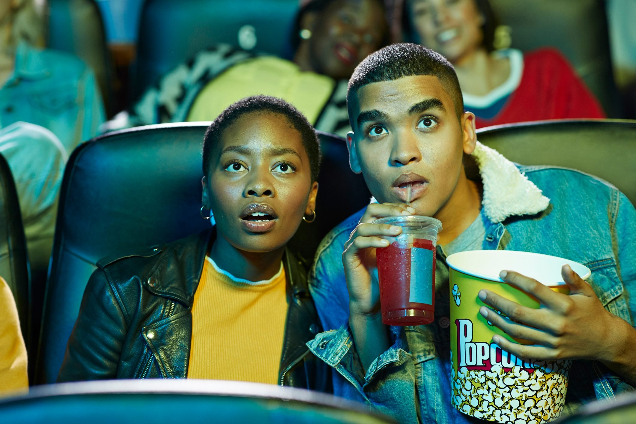 Surprised young man drinking soda while watching movie with friend in cinema hall