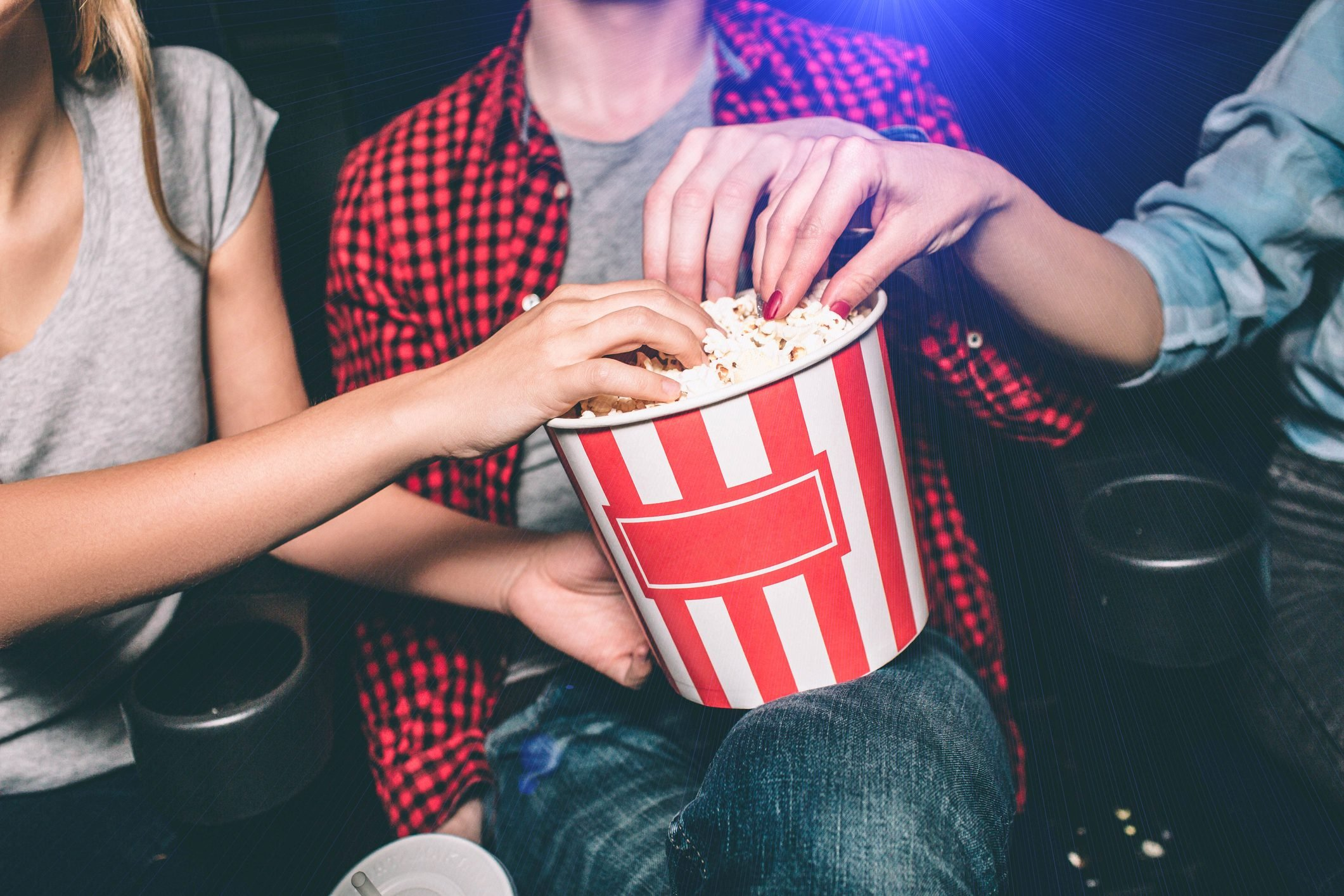Close up of red with white basket of popcorn that both girl and guy are holding. All of them are taking popcorn out of basket. Ð¡ut view.