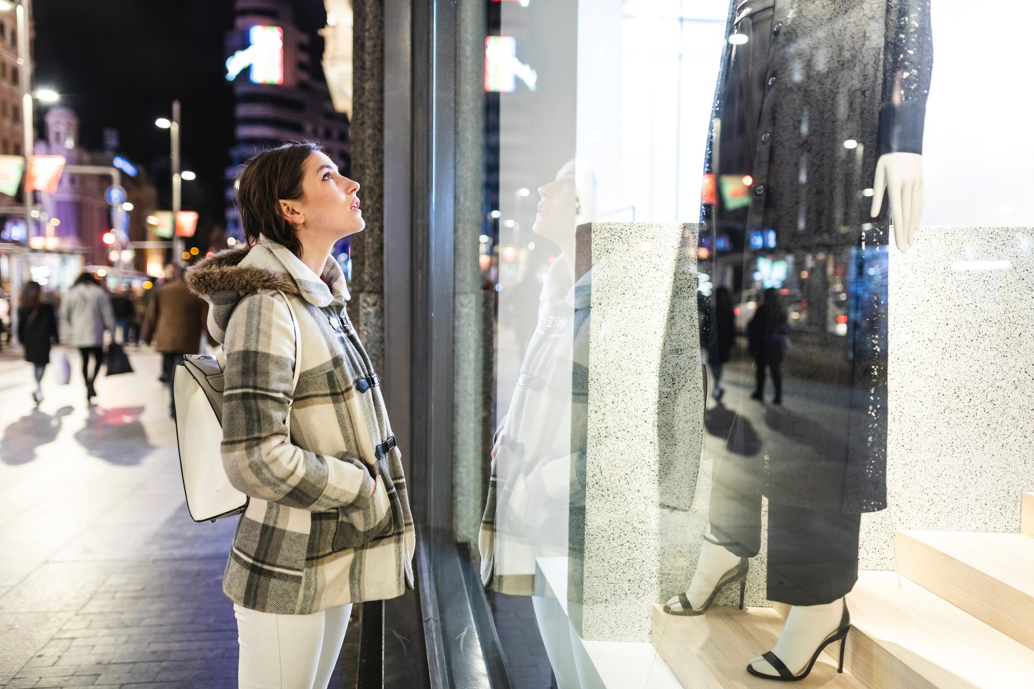 Spain, Madrid, young woman in the city at night next to Gran Via looking at a window shop