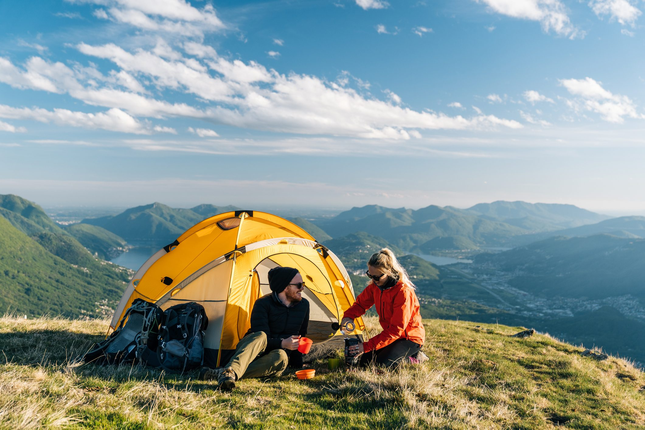 Couple camping on mountain top, prepare food and beverages next to tent