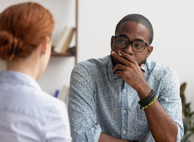 Doubtful african hr talking to caucasian applicant at job interview