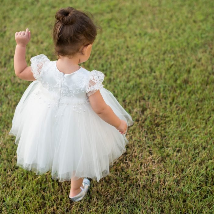 Toddler girl in a white dress on lawn