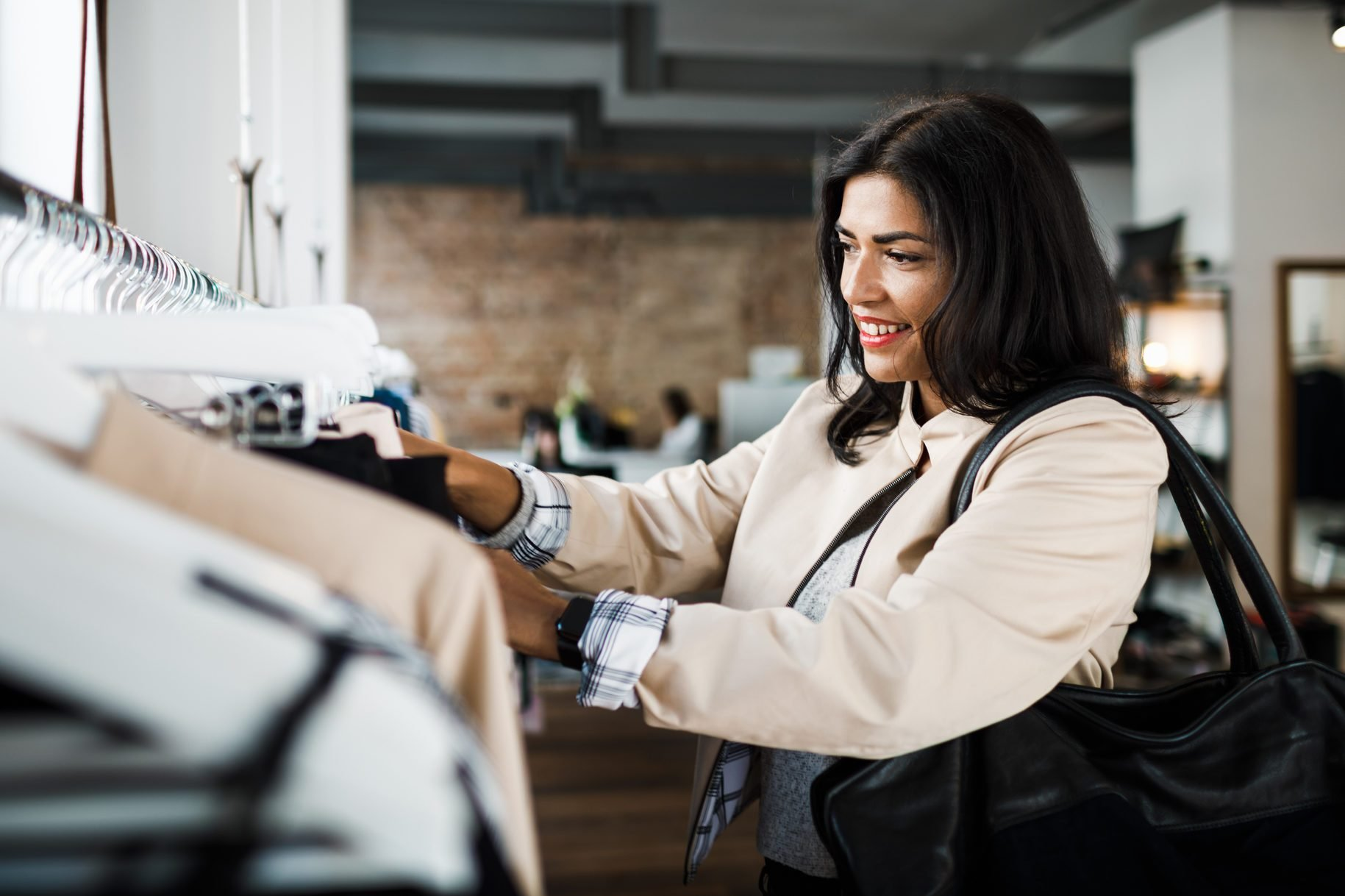 Woman Browsing Clothes In City Shop