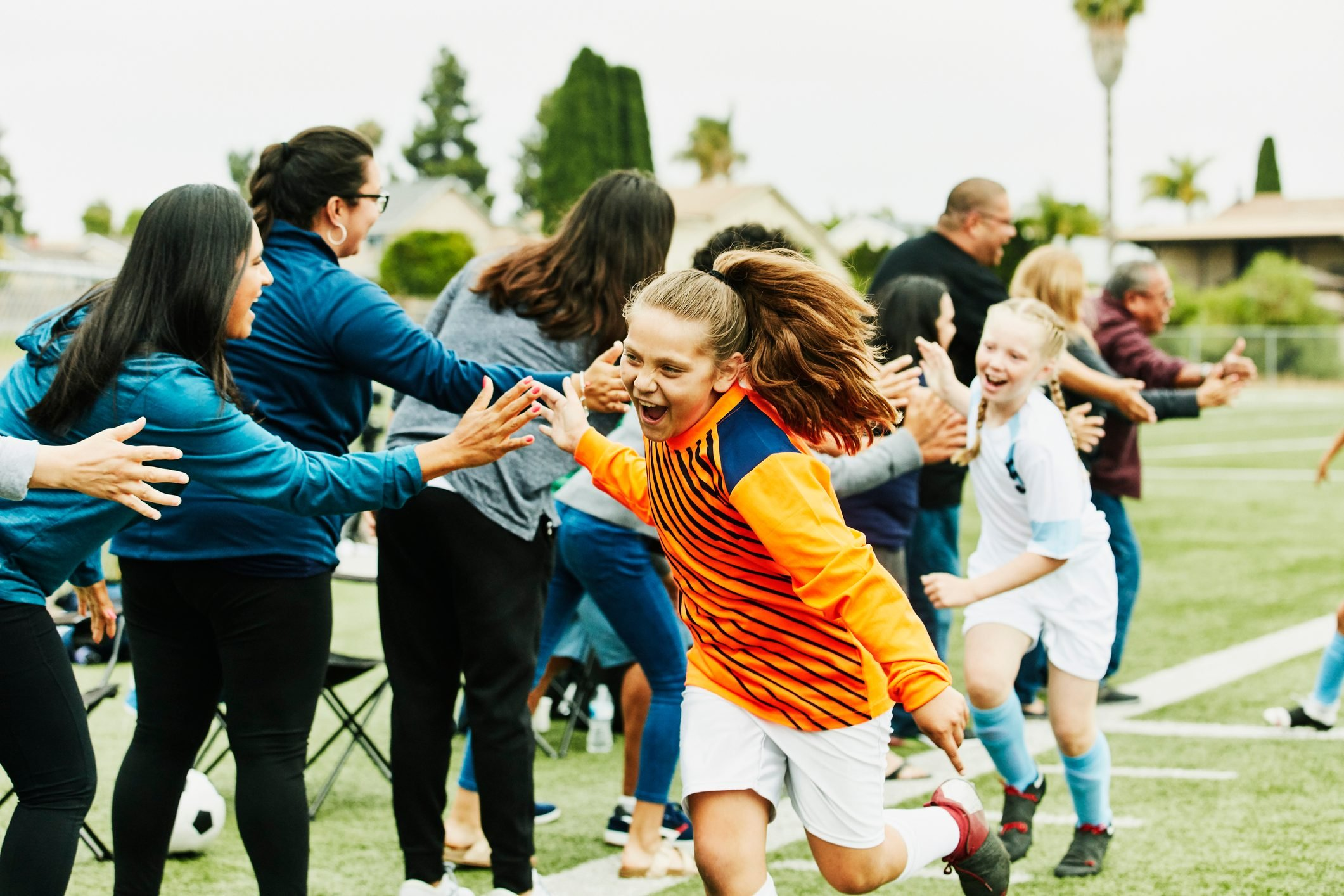 Young female soccer goalie high fiving parents on sidelines after soccer game