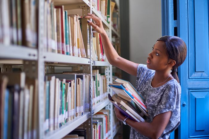 Young woman checking the books at the bookshelves at National library, Maputo, Mocambique