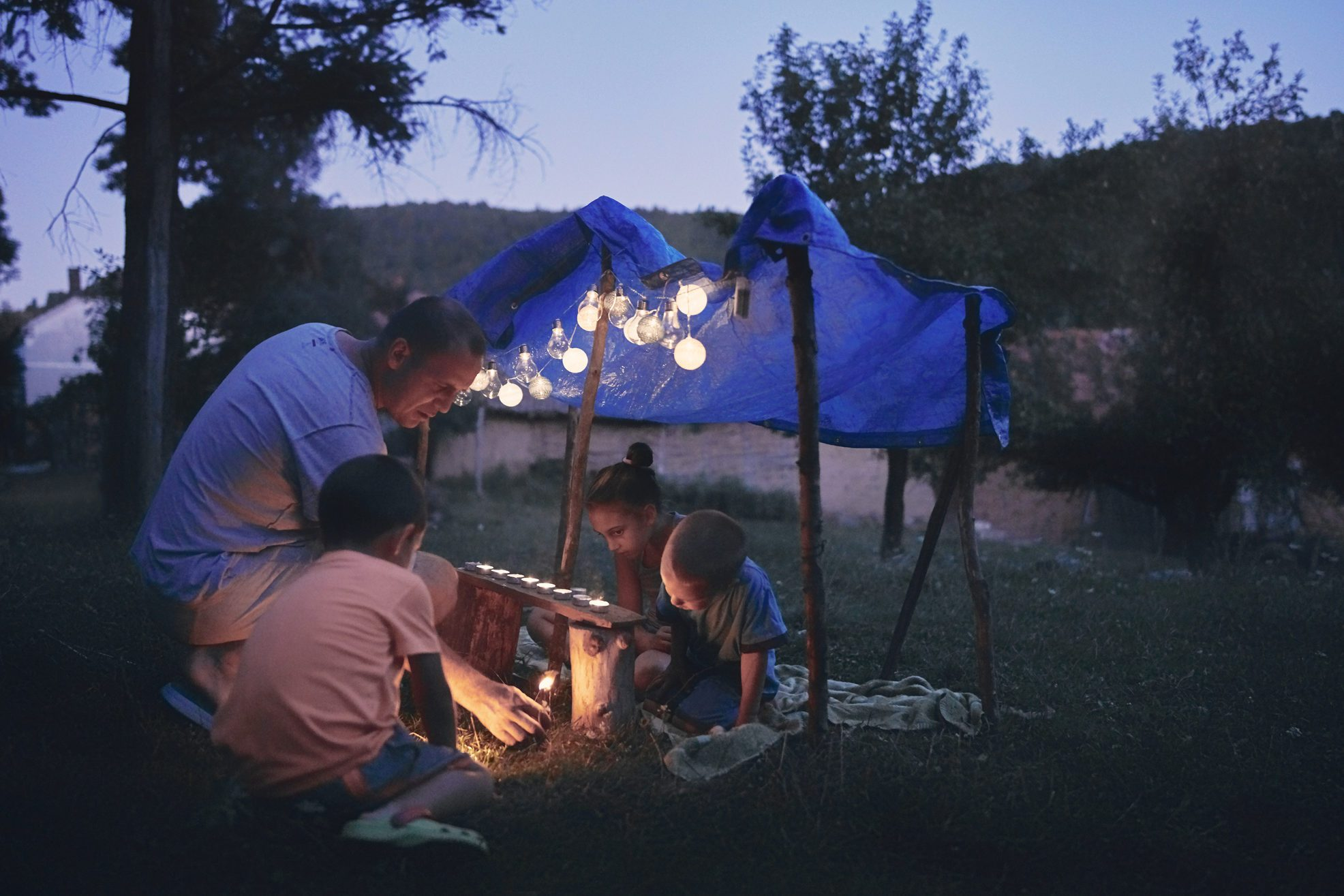 Father with children playing under their backyard tent.