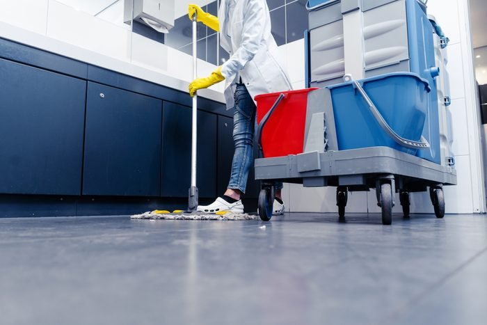 Low Section Of Man Cleaning Floor In Public Restroom