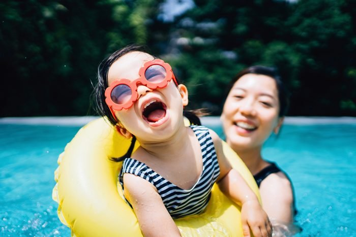 Happy Asian toddler girl with sunglasses smiling joyfully and enjoying family bonding time with mother having fun in the swimming pool in summer