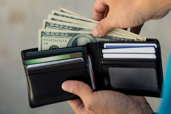 Cropped Image Of Man Holding Currency In Wallet