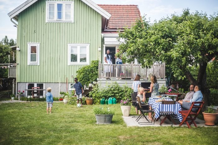 Mature friends having garden party while children playing in backyard during summer weekend